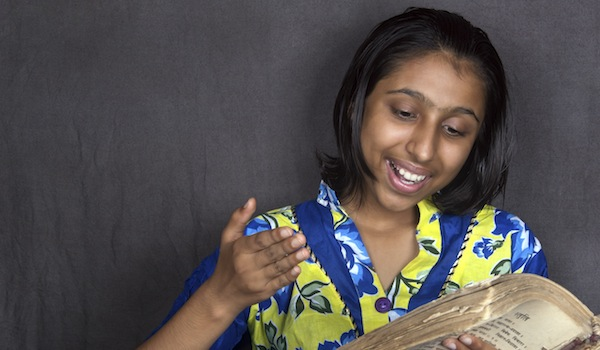 Cheerful Indian Girl Reading Holy Book