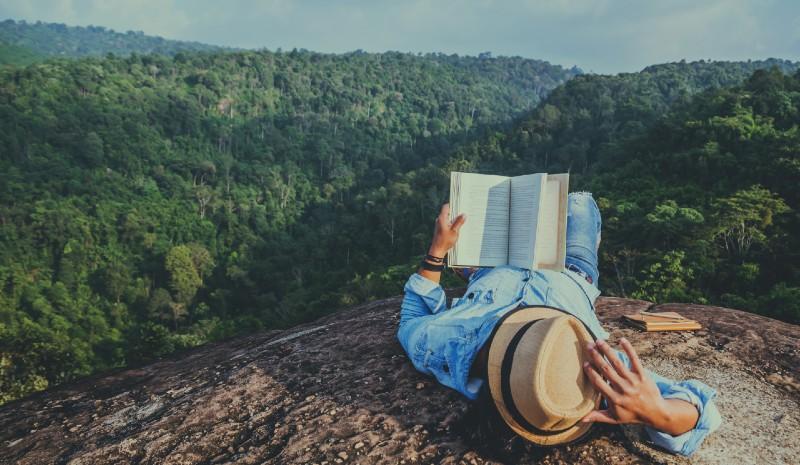 Man reading a book on a mountain